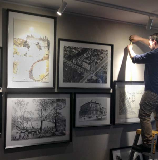 Image of Tom Ellis hanging a wall of artworks. Tom and Anita Ellis run Ellis Art Installation.